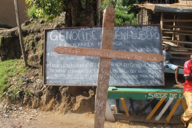 """Un tableau des habitants de Mutsanga, ville de Butembo sur lequel les habitants écrivent """" Génocide à Butembo - Beni"""" avec  un croix pour manifester la colère  du triple massacre de  personnes tuées par les  hommes armés assimilés aux Adf à Beni ce derniers temps. Credit photo/Nguru Wasingya Anselme"""